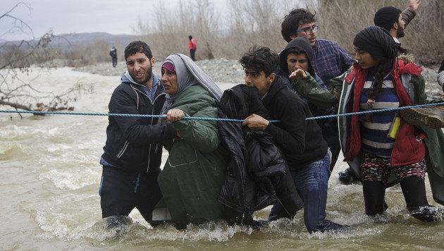 Auch alte Menschen und Kinder wagten die gef�hrliche Fluss�berquerung. (Bild: AP)