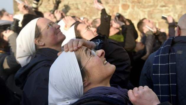 Schaulustige Nonnen und Touristen beobachten die Demontage der eine halbe Tonne schweren Statue. (Bild: APA/AFP/DAMIEN MEYER)