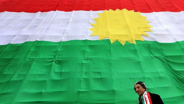 Ein syrischer Kurde vor der Flagge der kurdischen Volksgruppe (Bild: APA/AFP/Safin Hamed)