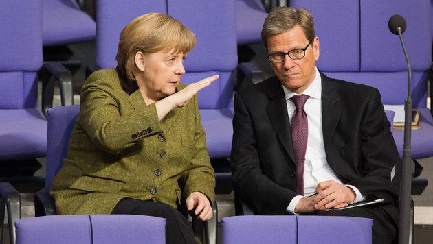 Unterredung zwischen Bundeskanzlerin Merkel und Westerwelle im Jahr 2013 im Bundestag (Bild: APA/dpa/Michael Kappeler)