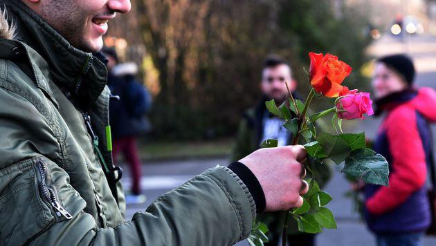 Nach den Ereignissen in der K�lner Silvesternacht verteilt ein Fl�chtling Blumen. (Bild: APA/AFP/PATRIK STOLLARZ)