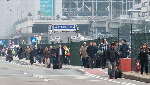 Passagiere verlassen den Flughafen in Brüssel. (Bild: APA/AFP/JOHN THYS)