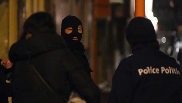 Maskierte Polizisten während der Razzia in Schaerbeek (Bild: APA/AFP/PATRIK STOLLARZ)
