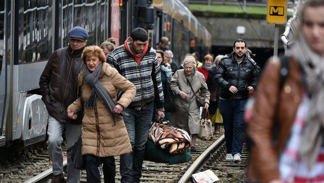 Fahrgäste verlassen nach Aufforderung der Polizei die Straßenbahn. (Bild: APA/AFP/PATRIK STOLLARZ)
