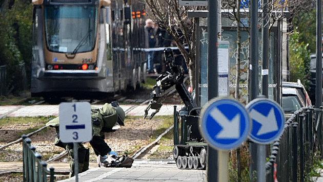Vorsichtig wird der Rucksack des Verhafteten in der Stra�enbahnhaltestelle inspiziert. (Bild: APA/AFP/PATRIK STOLLARZ)