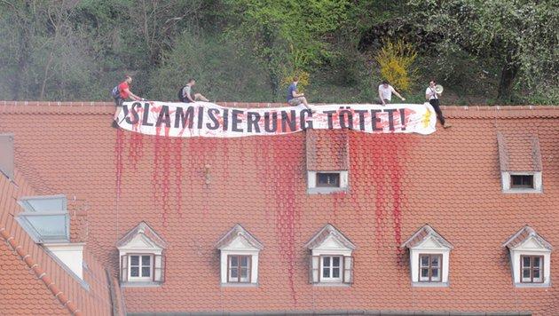 """Vier Männer entrollten auf dem Dach des Gebäudes ein Plakat mit den Worten: """"Islamisierung tötet"""". (Bild: APA/Grüne Steiermark)"""
