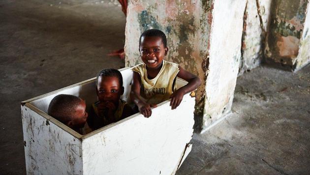 Kinder spielen in einer Holzkiste. Für sie ist der Alltag im zerbröselnden Betonbunker Alltag. (Bild: Alexander Pawloff)