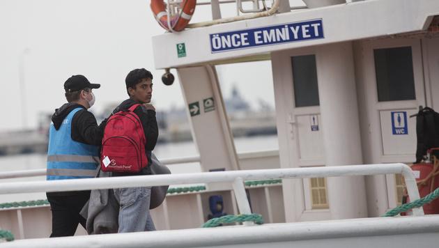 Migranten aus Pakistan werden auf Lesbos an Bord eines Schiffes Richtung Türkei gebracht. (Bild: AP)