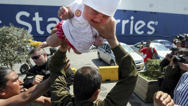 Das Baby weint bitterlich, als es der Mann über seinen Kopf hält. (Bild: AP)