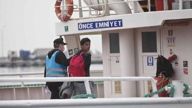 Ein Pakistaner wird auf Lesbos an Bord eines Schiffes gef�hrt, das ihn in die T�rkei bringt. (Bild: AP)