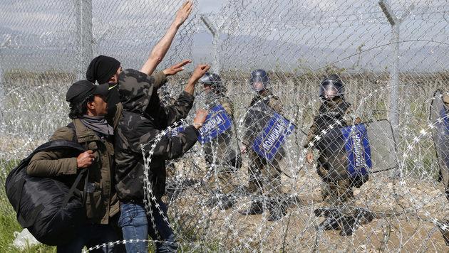 Flüchtlinge versuchen, ein Loch in den Zaun zu schneiden, dahinter warten bereits Polizisten. (Bild: ASSOCIATED PRESS)