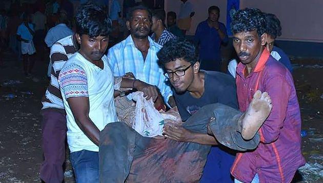 Helfer bringen einen verletzten Mann aus dem Inneren des Tempels. (Bild: APA/AFP/STR)