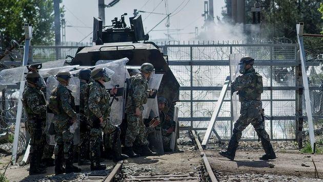 Mazedonische Grenzpolizisten gehen vor Steinwürfen in Deckung. (Bild: APA/AFP/ROBERT ATANASOVSKI)