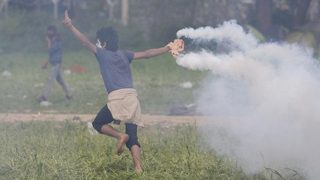 Ein Flüchtling beim Zurückwerfen einer Tränengasgranate (Bild: ASSOCIATED PRESS)