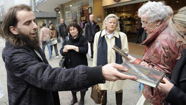 Ein deutscher Islamist verteilt in Wuppertal den Koran. (Bild: dpa/Henning Kaiser)