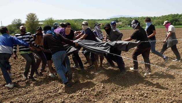 Flüchtlinge beim Versuch, den Grenzzaun in Idomeni zu beschädigen (Bild: APA/AFP/DANIEL MIHAILESCU)