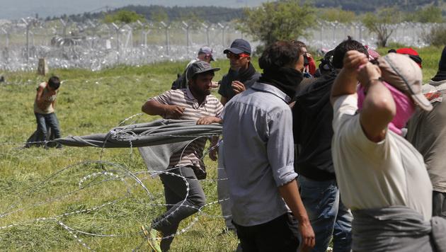 Flüchtlinge am Grenzzaun in Idomeni (Bild: AP)