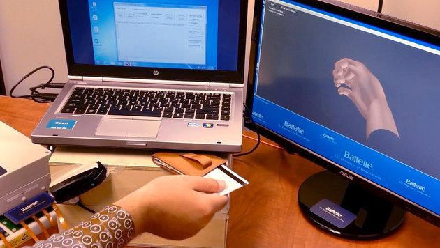 Chip im Gehirn steuert Hand von Gelähmten (Bild: AFP)