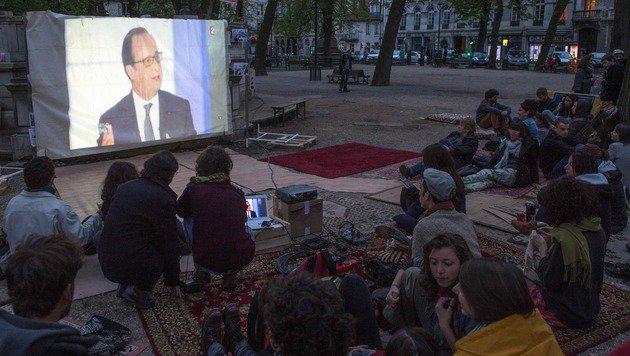 Viele Demonstranten verfolgen den TV-Auftritt von Hollande im Freien. (Bild: AFP)