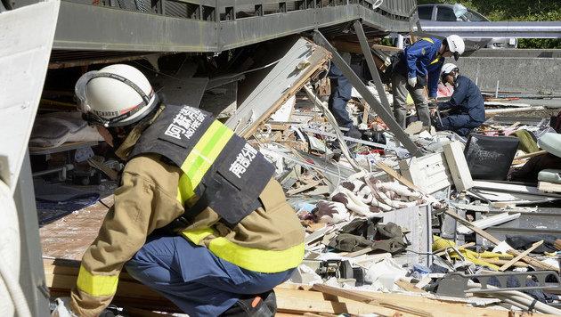 Helfer suchen unter einem eingest�rzten Haus nach Versch�tteten. (Bild: Associated Press)