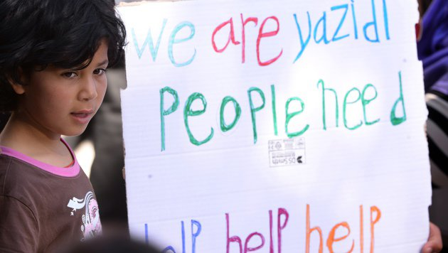 """Jesidisches Flüchtlingskind vor einem Plakat mit der Aufschrift """"Wir brauchen Hilfe"""" (Bild: Associated Press)"""