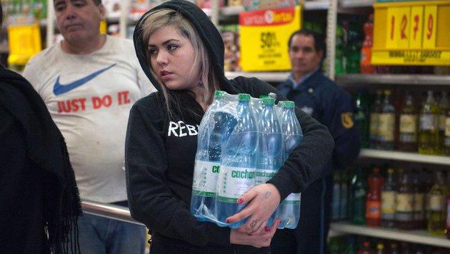 In Supermärkten decken sich die Menschen mit Trinkwasser ein. (Bild: APA/AFP/Vladimir Rodas)