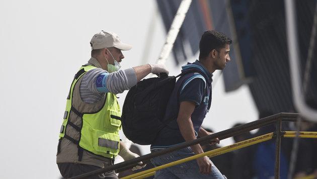 Ein Frontex-Beamter begleitet einen Flüchtling an Bord einer Fähre. (Bild: ASSOCIATED PRESS)