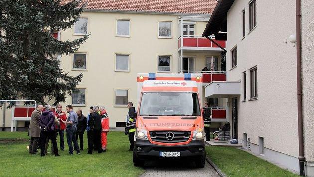 Einsatzkräfte vor dem Haus, in dem die Frau gefunden wurde (Bild: APA/AFP/dpa/Josef Reisner)