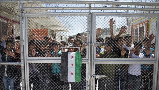 Flüchtlinge hinter einem versperrten Tor des Camps Moria auf Lesbos (Bild: ASSOCIATED PRESS)
