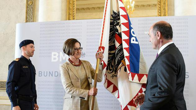 Feierliche Amtsübergabe im Innenministerium: Mikl-Leitner überreicht Sobotka die Ressort-Fahne. (Bild: APA/HELMUT FOHRINGER)