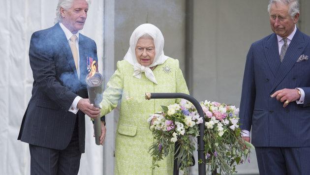 Die Queen entzündet an ihrem 90. Geburtstag eine Fackel. (Bild: AP)