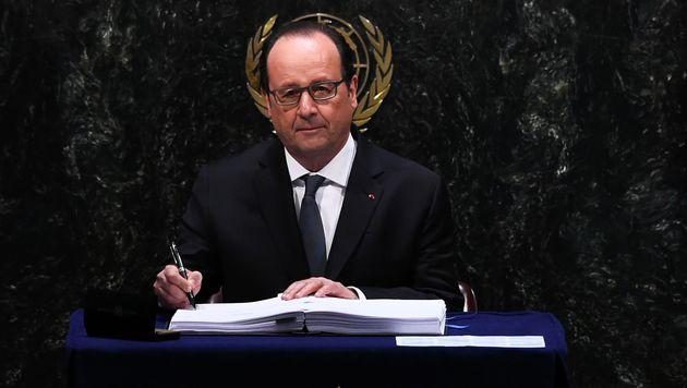Francois Hollande unterzeichnet das Klimaabkommen. (Bild: APA/AFP/JEWEL SAMAD)