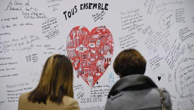 Fahrgäste lesen Botschaften von Überlebenden und Angehörigen der Opfer in der Station Maelbeek. (Bild: APA/AFP/JOHN THYS)