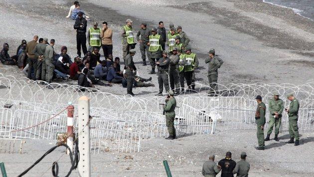 Flüchtlinge vor dem Grenzzaun zu Ceuta (Bild: EPA)