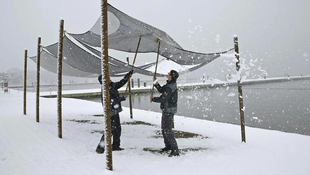 Zwei Männer bei Schneeräumarbeiten im Klagenfurter Strandbad (Bild: APA/GERT EGGENBERGER)
