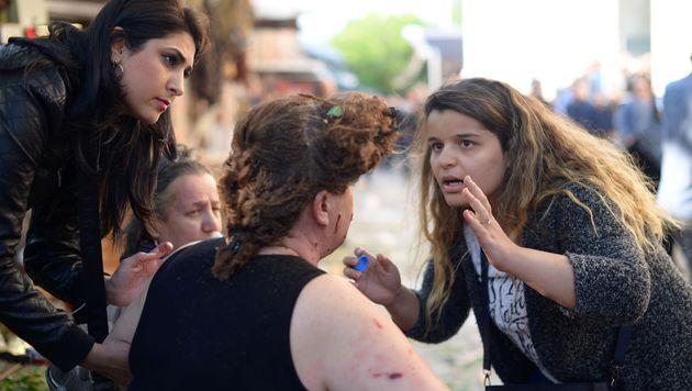 Passanten leisteten nach der Explosion sofort Erste Hilfe. (Bild: APA/AFP/Onur Yurtsever)