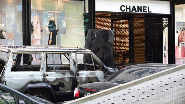 Der ausgebrannte Wagen vor dem Chanel-Shop (Bild: APA/AFP/Eric Feferberg)