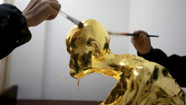 Das Auftragen des Blattgoldes auf den mumifizierten Mönch (Bild: Associated Press)