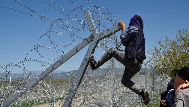 16.4.: Ein vermummter Migrant versucht den Grenzzaun zu Mazedonien zu überwinden. (Bild: APA/AFP/Daniel Mihailescu)