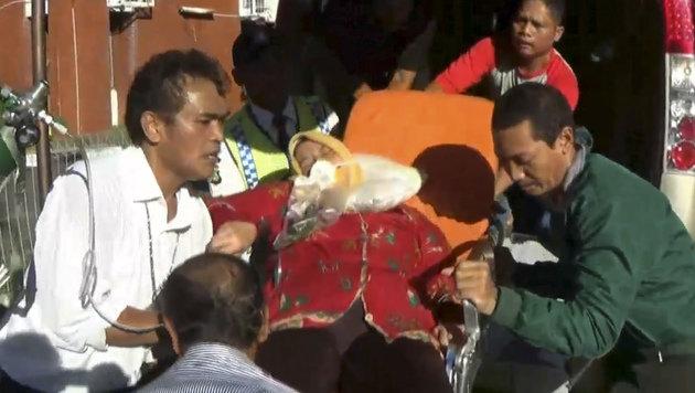 Eine verletzte Passagierin wird von Rettungskr�ften versorgt. (Bild: ASSOCIATED PRESS)