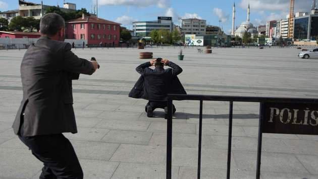 Szenen wie im Wilden Westen: Ein Polizist richtet seine Waffe auf den mutmaßlichen Attentäter. (Bild: APA/AFP/CUMHURIYET DAILY NEWSPAPER/HANDOUT)