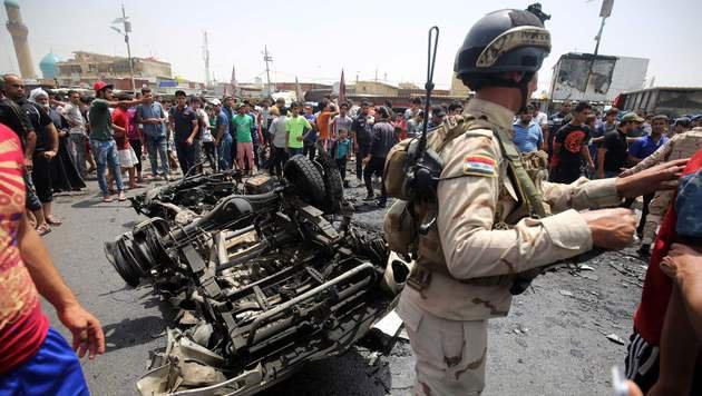 Irakischer Soldat dr�ngt Schaulustige vom Tatort in Sadr-City weg. (Bild: APA/AFP/AHMAD AL-RUBAYE)