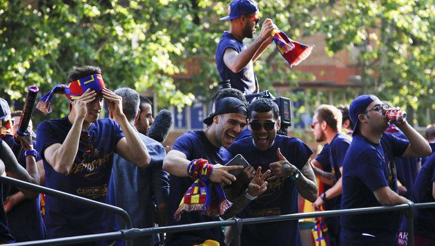 Die Barca-Superstars fuhren im offenen Bus durch die Stadt und ließen sich feiern. (Bild: AP)