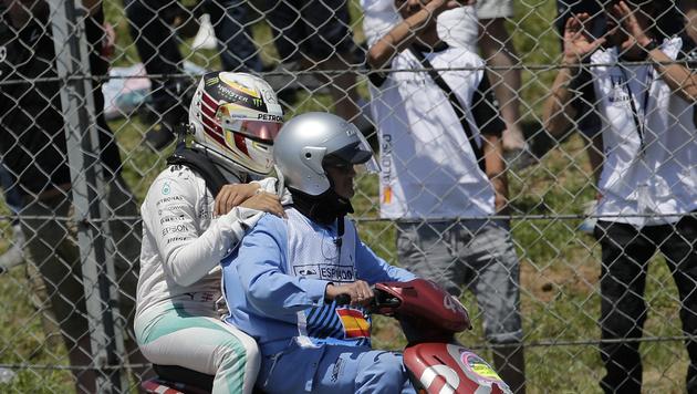 Nach dem Unfall wurde Hamilton per Motorroller in die Box gebracht. (Bild: AP)