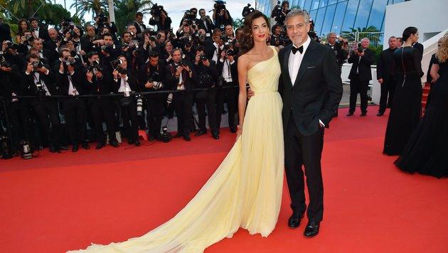 George Clooney hält seine Frau Amal im Arm, die ein Kleid von Atelier Versace gewählt hat. (Bild: AFP)