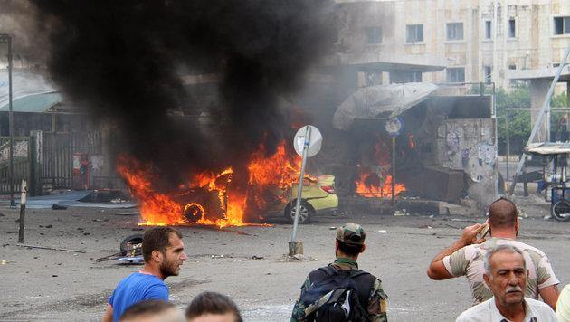Im syrischen Tartus brennt ein Auto, mit dem sich ein Attent�ter in die Luft jagte. (Bild: Associated Press)
