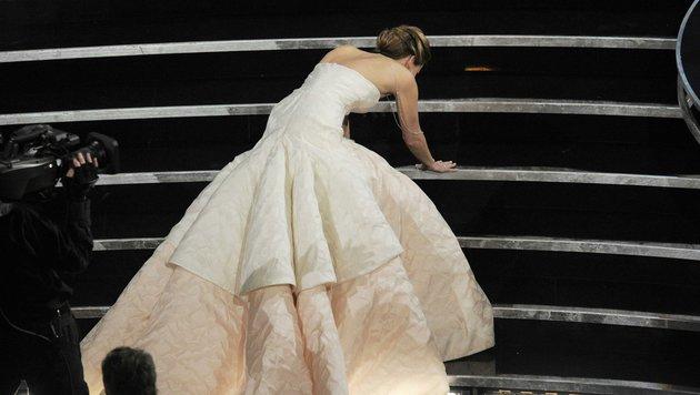 Jennifer Lawrence stolpert ihrem Oscar entegegen. (Bild: Chris Pizzello/Invision/AP)