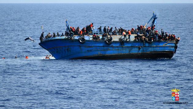Aufnahme der italienischen Marine: Das völlig überladene Fischerboot kenterte vor Libyens Küste. (Bild: AP)