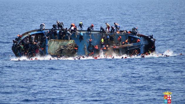 Die Aufnahme der italienischen Marine zeigt ein kenterndes Flüchtlingsboot. (Bild: AP)
