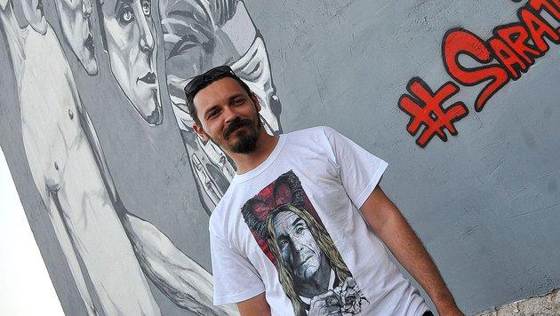 Der bosnische Musiker Vedad Trbonja vor dem Wandbild (Bild: APA/AFP/Elvis Barukcic)